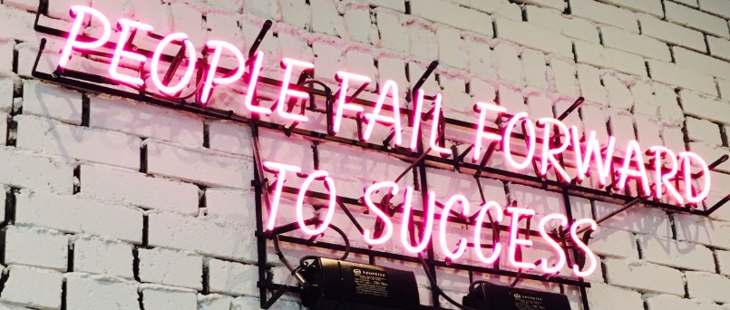 neon sign: people fail forward to success