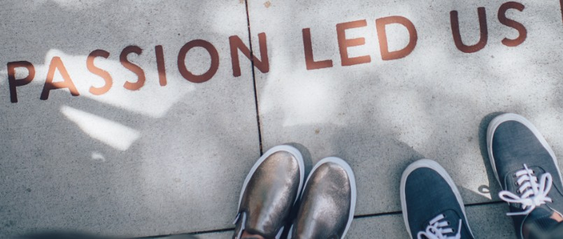 """passion led us"" written on sidewalk beside two pairs of feet"