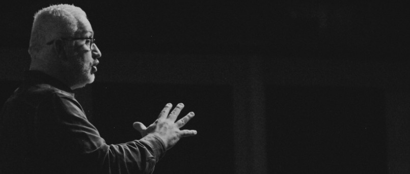 black and white image of man speaking and gesturing