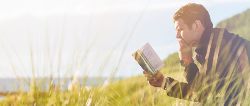 man reading book in tall grass