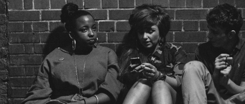 teenagers sitting against a brick wall